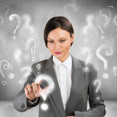 Business woman with question symbols around her. Choosing one and pressing on it photo