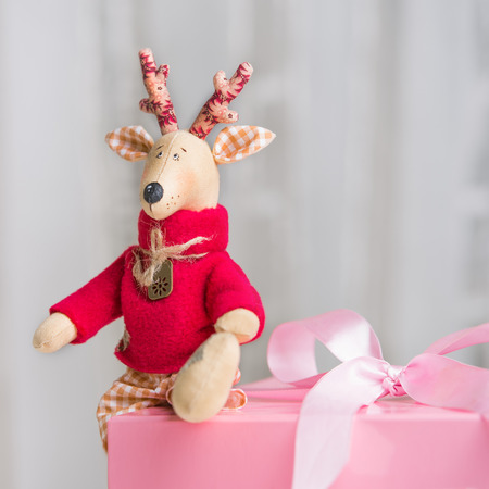 Handmade toy vintage Christmas deer sitting on the pink gift box photo