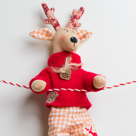 Handmade vintage Christmas deer hanging on a ribbon on white background photo