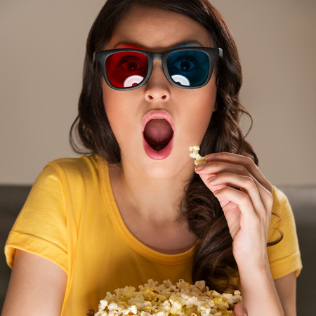 Beautiful girl watching movie with 3d glasses and eating popcorn. She is very expressive photo