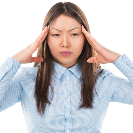 Beautiful Asian business woman with headache holding head in pain over white background photo
