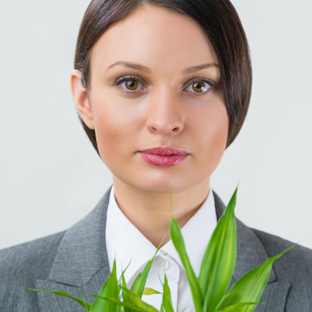 Adult business woman holding lucky bamboo plant symbol of success. Business growing concept photo