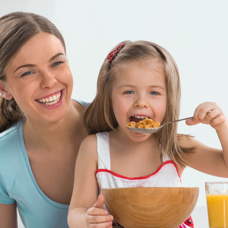 eating breakfast: Portrait of adorable young girl and mother in a playful mood having breakfast at home