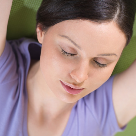 Portrait of a young fitness woman lying on a yoga mat and exercising photo
