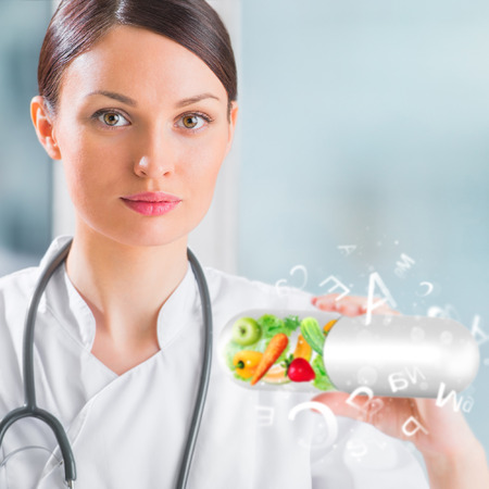 microelements: Healthy life concept. Female medical doctor holding vitamins