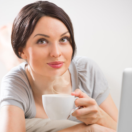 A young woman lying on the floor in front of her laptop with cup of tea or coffee photo