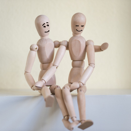 Wooden people sitting at home and hugging. People relationship concept. Drawn faces photo
