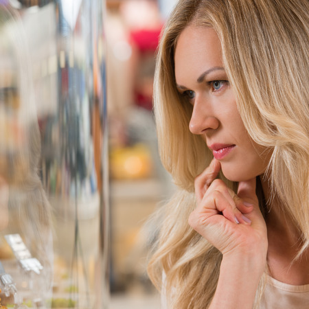 Woman shopping at the supermarket, standing near glass showcase and thinking what to choose photo