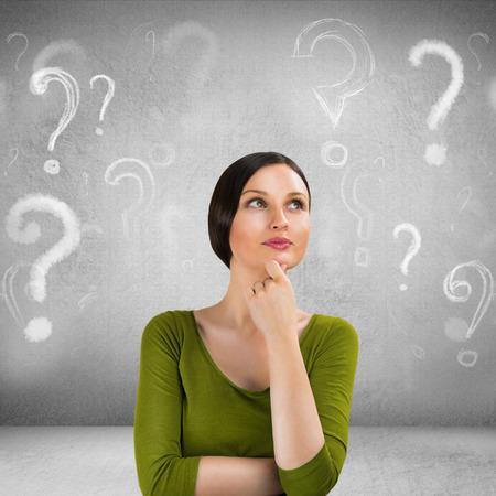 preguntando: Mujer hermosa con la expresión que pregunta y signos de interrogación sobre su cabeza