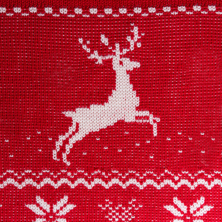 Real red knitted background with white Christmas deers and snowflakes photo