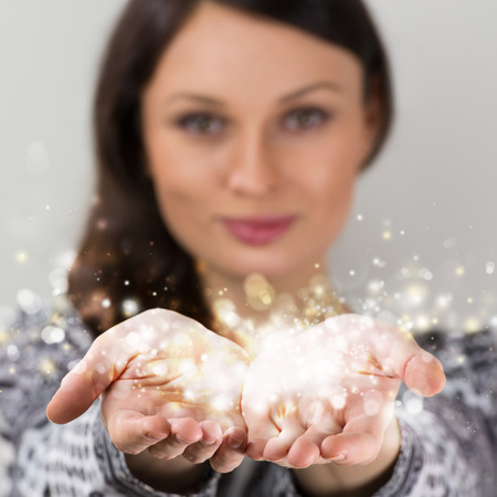 giving hands: Pretty young brunette woman smiling against gray background with magic sparkle in her hands cupped together