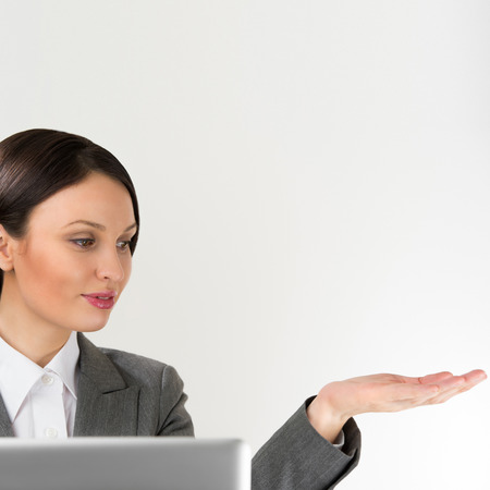 Adult pretty business woman making presentation of new product. Blank copyspace above her arm photo