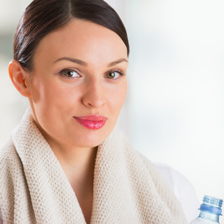 Portrait of confident young woman in sportswear holding a water bottle in gym photo