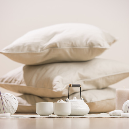 Teapot and cups with aromatic sticks and candles in front of pillows and decorations at home photo