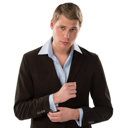 Portrait of a confident young male executive buttoning his cuff on white background Stock Photo - 27585144