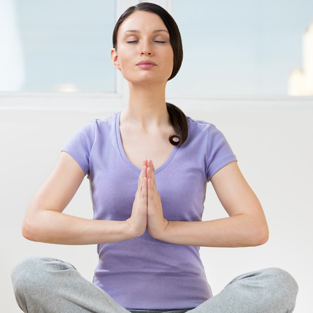 Portrait of beautiful young woman doing yoga exercise - Meditating photo