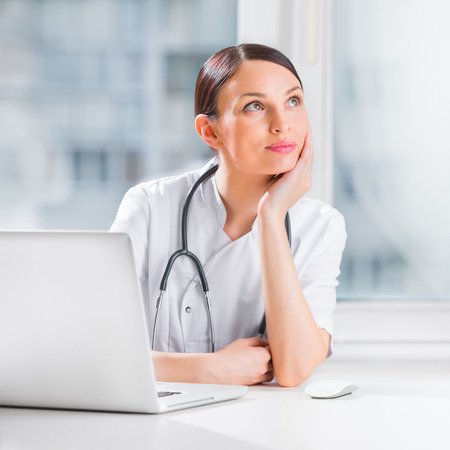 Portrait of a female doctor using her laptop computer at clinic and daydreaming photo