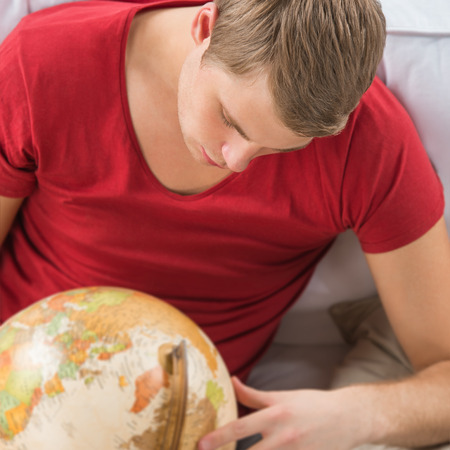Portrait of young handsome caucasian man at home looking at globe and planning his trip photo