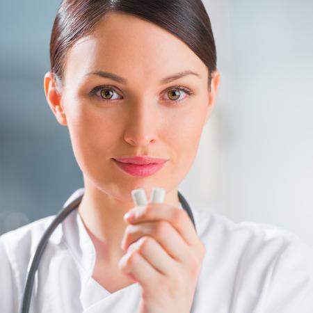 goma de mascar: Joven médico dentista femenina sosteniendo la goma de mascar y sonriente. Concepto de atención dental Foto de archivo