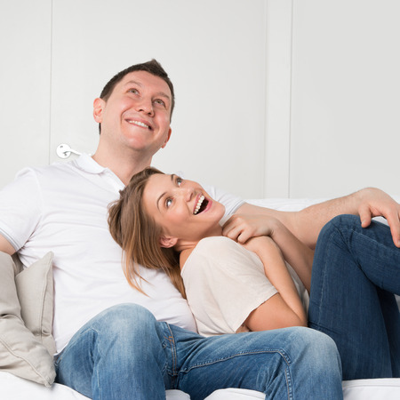 Young couple on the sofa in love planning future and having fun photo