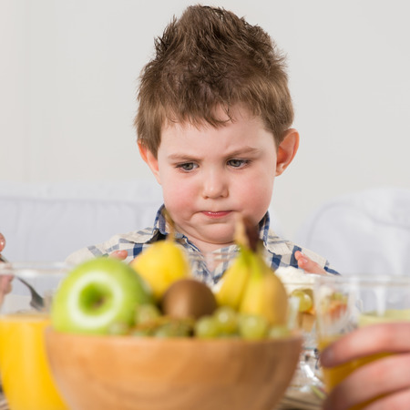 capricious: Child on breakfast - looking capricious while sitting at home near table