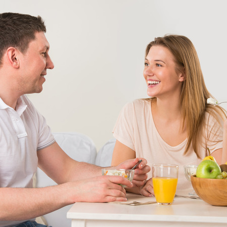 Happy couple eating at home - having breakfast together photo
