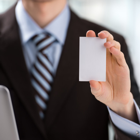 Closeup of torso of confident business man wearing elegant suit sharing his blank business card at his workplace photo