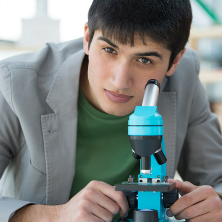 Male student in laboratory looking at camera while working with microscope and making notes