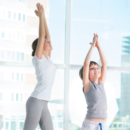 Portrait of healthy female and her son practicing physical exercise at gym photo