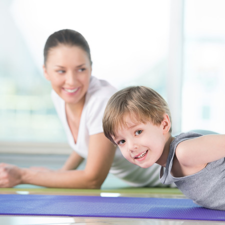 Healthy morning stretching - woman with son doing gymnastic exercise at home photo