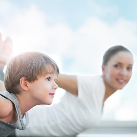 Familia saludable - madre e hijo haciendo ejercicios contra el cielo azul