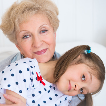 Lovely little girl with her grandmother having fun and happy moments together at home photo