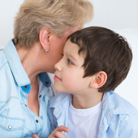 Grandmother with grandson having fun at home - whispering secrets photo