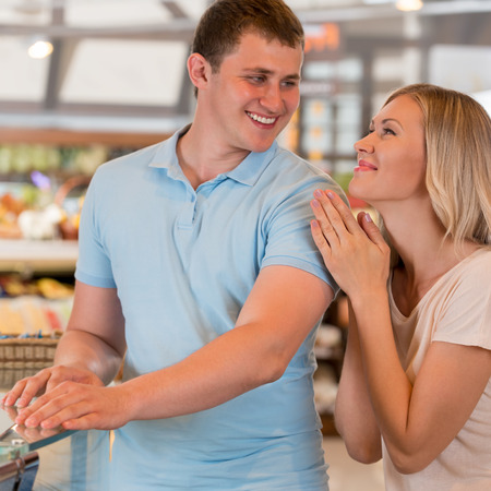 Young couple shopping at supermarket - having fun together photo