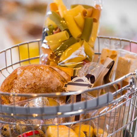 Grocery store. Supermarket basket full of different food - cheese, bread, jam, coockies, pasta and other photo