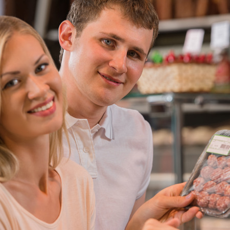 meat lover: Couple shopping at the supermarket buying meat Stock Photo