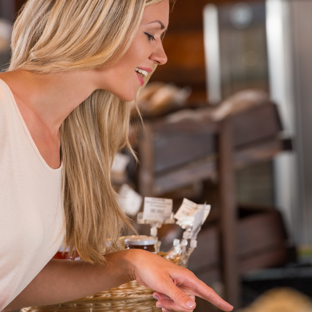 Positive young woman at the bakery store choosing what she wants to by and placing order to seller photo