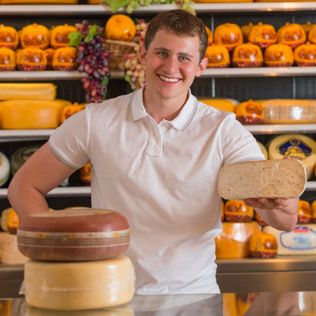 Handsome male owner of a cheese store standing with cheese pieces looking at the camera with a confident smile and offering his product photo