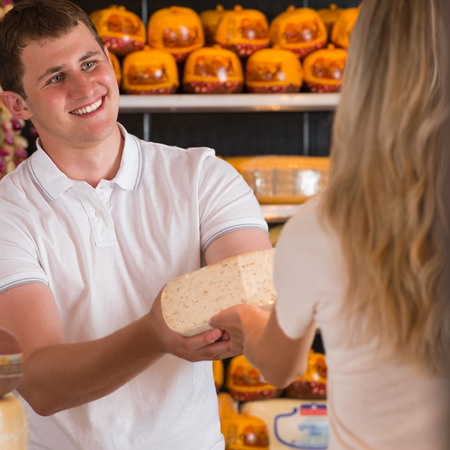 Male salesman in cheese store with a female customer talking about his products and helping to choose delicious cheese photo