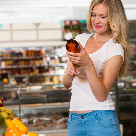Woman shopping at the supermarket, reading information on natural juice bottle photo