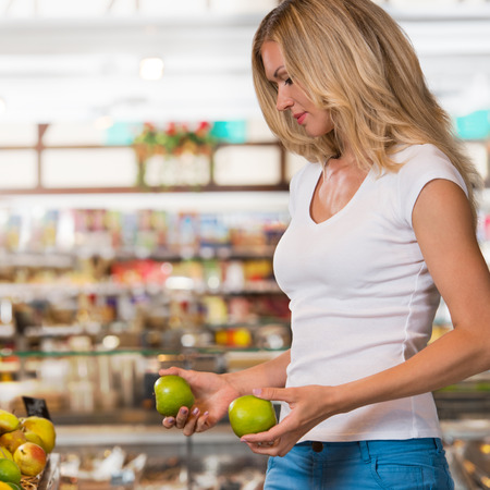 Cute happy brunette shopping in a grocery store, organic food section photo