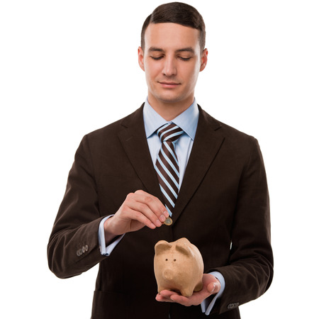 pennypinching: Young happy business man putting money in the piggybank over white background Stock Photo