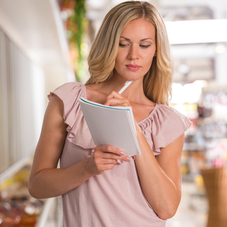 Shopping list - woman using shopping list at grocery store photo