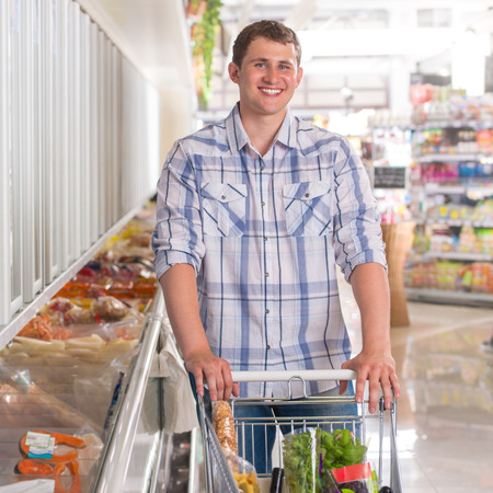 Handsome young man shopping for diary products at a grocery store or supermarket photo