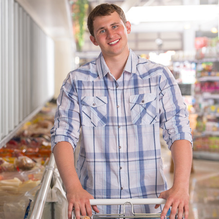 Young man shopping for frozen food in a grocery store photo