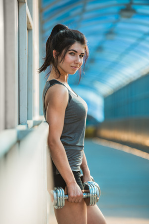 sweat girl: Athletic woman pumping up muscles with dumbbells outdoors in the city