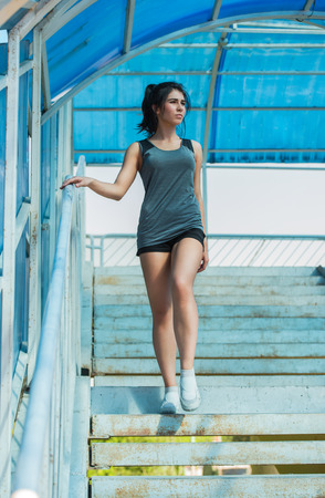 Healthy lifestyle sports woman walking on stairs of city bridge photo