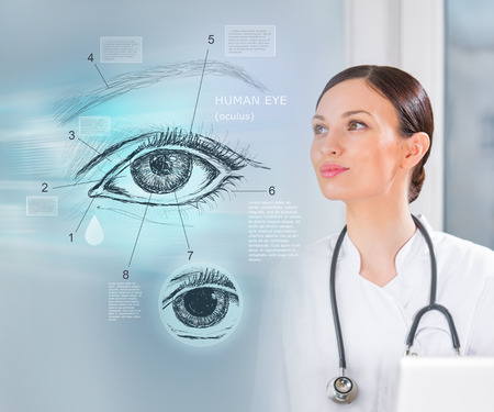 Female medical doctor working with virtual interface examining human eye photo