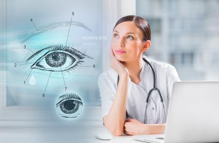 ojo humano: Mujer m�dico de trabajo con interfaz virtual examinar ojo humano Foto de archivo