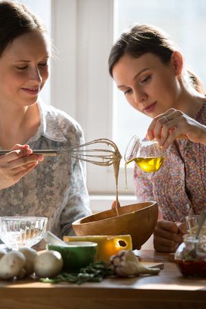 mujeres cocinando: Las mujeres que cocina la pizza en casa. Dos mujeres amasan la pasta Foto de archivo